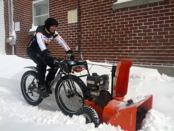 Last snow storm in Old Longueuil, clearing snow from the entrance to the bike shop Andre Cycle & Sport with fat bike