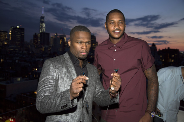 SMS Audio CEO Curtis '50 Cent' Jackson shows off a pair of the new SMS Audio BioSport In-Ear Headphones powered by Intel alongside NY Knicks basketball star Carmelo Anthony