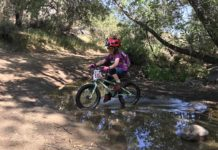 bikerumor pic of the day Kerry Waldman with Grom crossing the creek on her pedal bike.