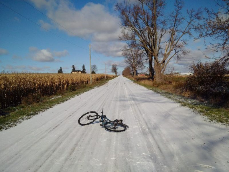 bikerumor pic of the day black bicycle laying on gravel road with dried corn fields on one side and blue skies ahead north of Woodstock, Ontario.