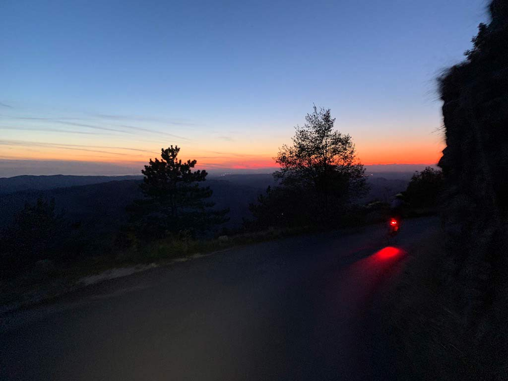 sunset view riding down a switchback road off nanos plateau in slovenia