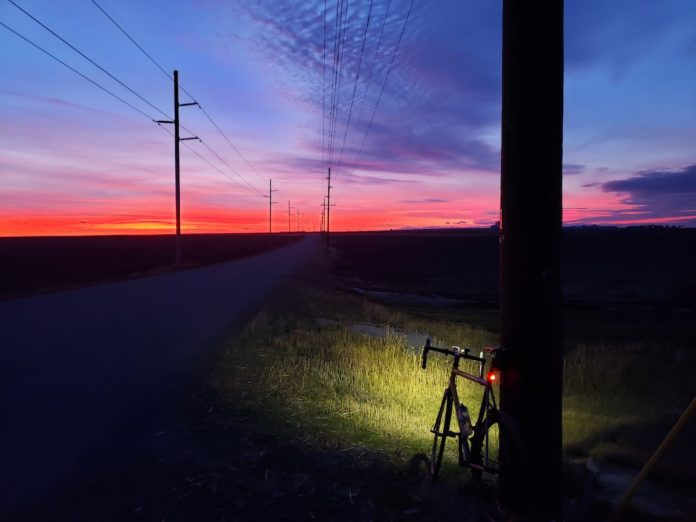 Bikerumor pic of the day of a bicycle leaning against a telephone pole with light beam in the grass and orange and blue sunset in the distance.