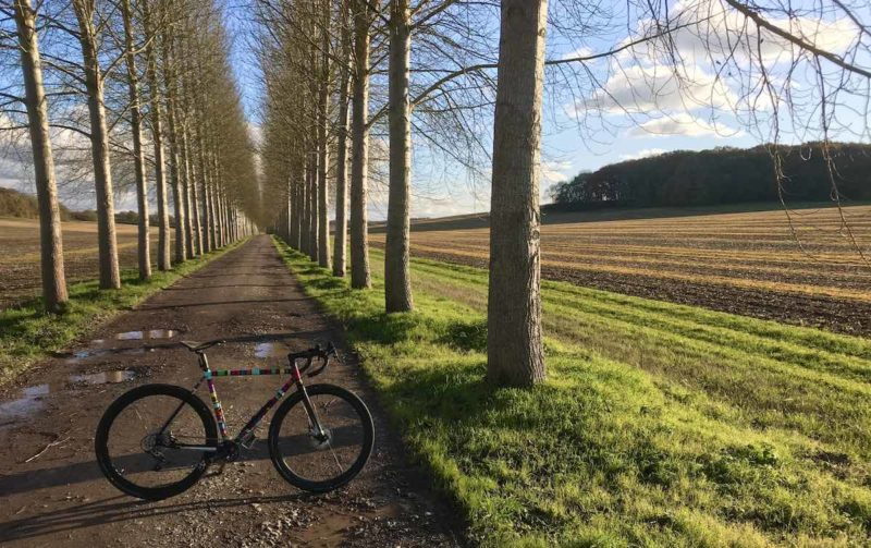 bikerumor pic of the day bicycle on a gravel path with a line of trees on either side and a field to the right, Near the village of Boxford, West Berkshire, England.