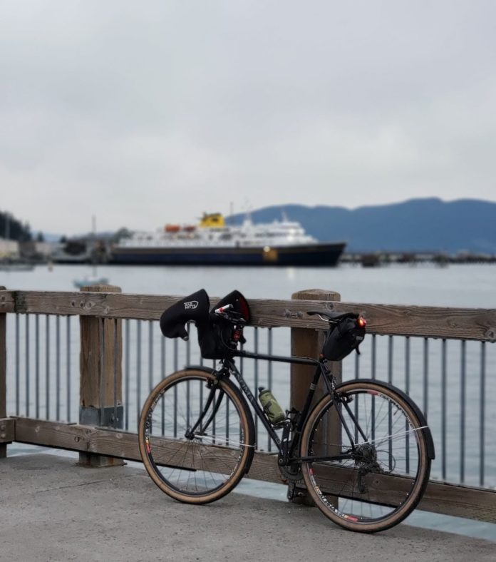 bikerumor pic of the day: touring bicycle leaning up against a fence overlooking the Alaska ferry in the terminal.