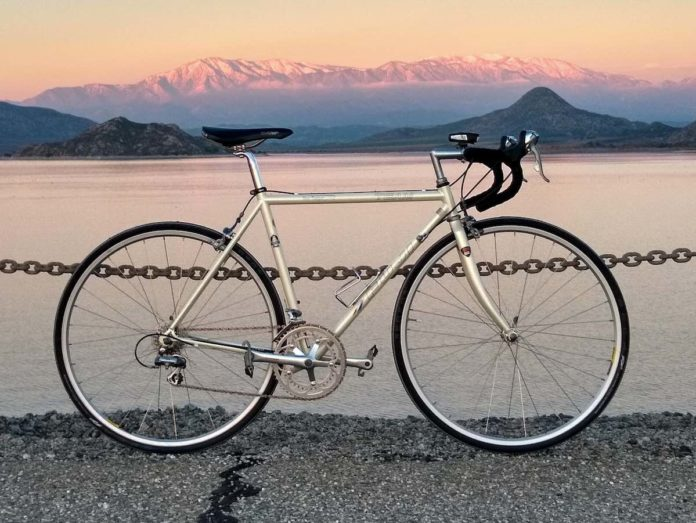 bikerumor pic of the day silver fuji bicycle in front of lake perris in california as the sun sets it gives the mountains and lake a pink and purple glow.
