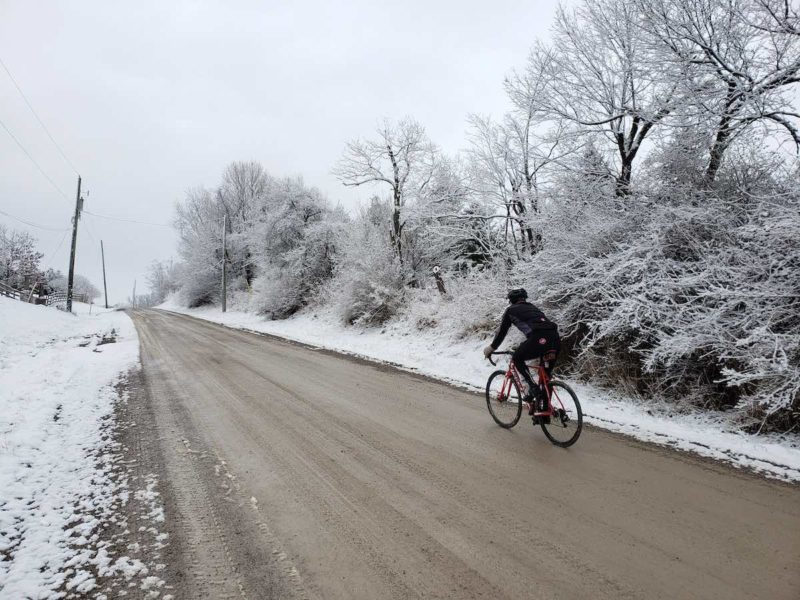 bikerumor pic of the day cyclist riding up a packed dirt road with snow covering the trees and edges of the road.