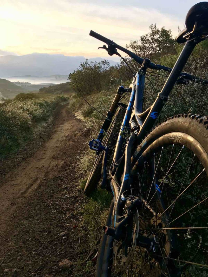 bikerumor pic of the day open trail on the Dos Vientos trail in california, right after sunrise. Mountain bike leaning against berm on dirt trail as morning light fills the sky.