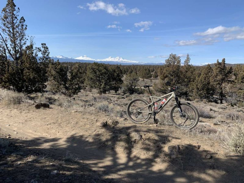 bikerumor pic of the day mountain biking in Maston trail system in Central Oregon. mountain bike on dirt trail with pine scrub behind it and snowy mountain tops in the distance.
