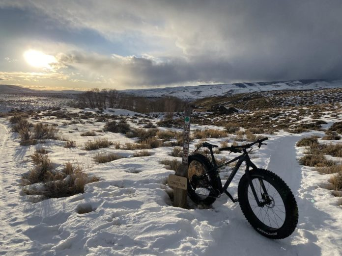 bikerumor pic of the day hartman rocks trail near gunnison colorado. fat tire mountain bike sitting in snow on a wide open valley covered in snow and grassland.