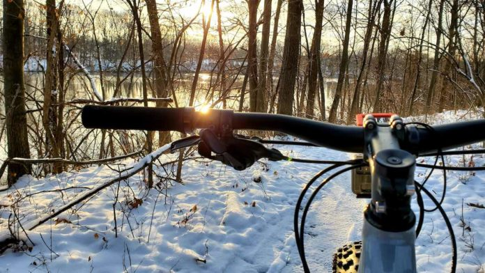 bikerumor pic of the day sunrise in Anderson park Trail in Lansing, MI. view from cockpit of a mountain bike looking over snowy trail as sun rises through trees over the lake.