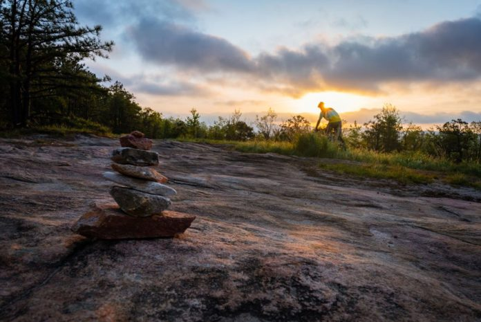 bikerumor pic of the day dear rock, dupont state park north carolina. mountain biker is in the distance riding on slick rock with the sun setting behind them and a cairn in the foreground.