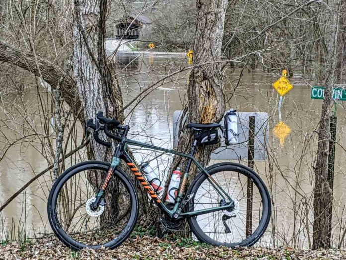 bikerumor pic of the day niner bicycle against a bare tree with a flooded street behind it on the little miami bike trail in southern ohio.