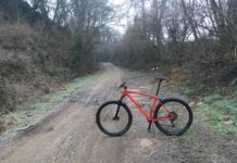 bikerumor pic of the day valle sauglio italy dirt road with red bicycle posed sideways, winter scrub brush on either side of the road.