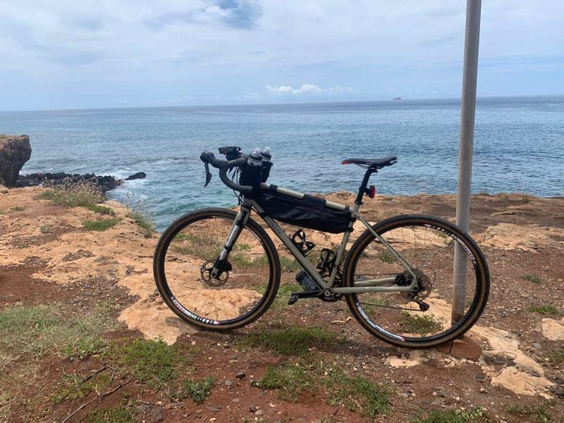 bikerumor pic of the day specialized bicycle on a rough sandy shoreline with ocean behind it and a ship in the distance off electric beach on oahu, hawaii.