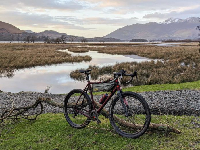 bikerumor pic of the day ruut bicycle on a grassy landing in front of a lake surrounded by wetlands and skiddaw mountain in the distance.
