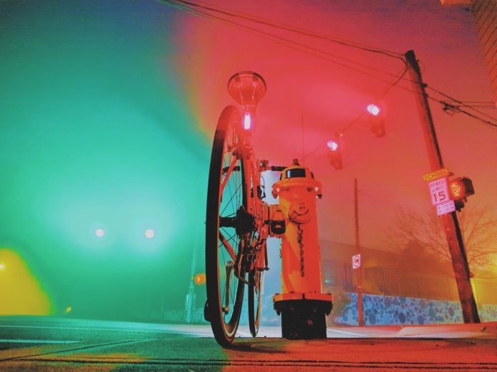 bikerumor pic of the day foggy morning commute in covington kentucky, a bicycle leaning against a fire hydrant by the street with fog making the street lights glow green on one side of the photo and red on the other side.