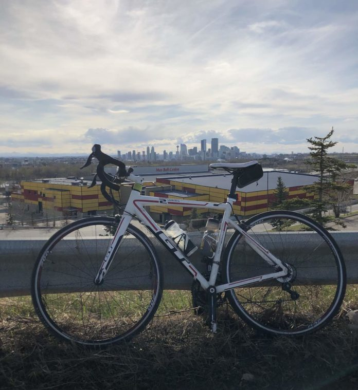 bikerumor pic of the day gt bicycle leaning against road barrier with the city of calgary alberta canada in the distance.
