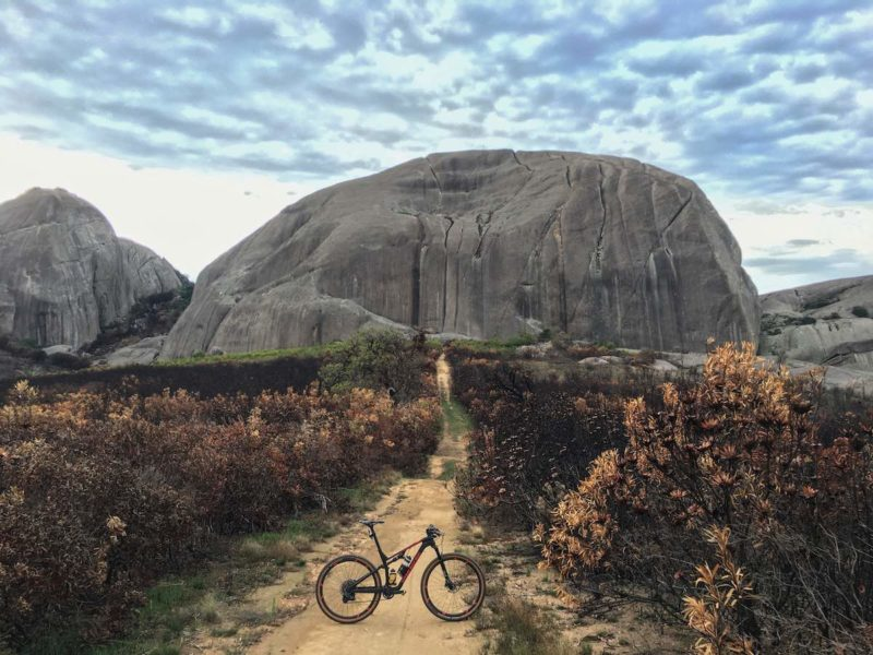 bikerumor pic of the day mountain bike posed on a dirt path leading up to large igneous rock formation like a tortoise shell with burnt brush on either side, paarl mountain in south africa.