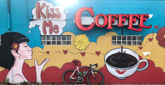 bikerumor pic of the day bicycle posed in front of a mural for a coffee shop called Kiss Me Coffee showing a woman with white skin and black hair blowing kisses to the coffee cup.