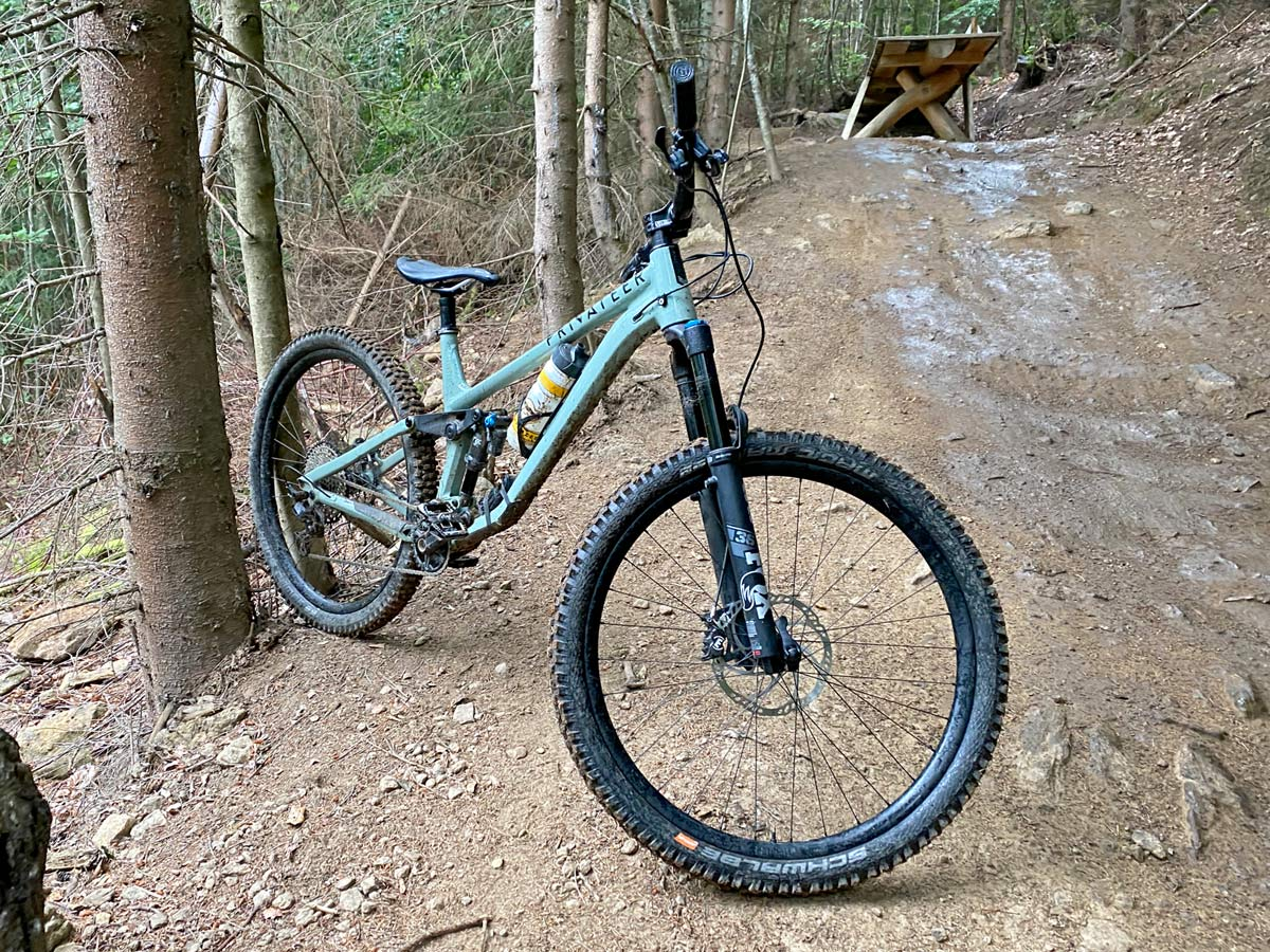 Privateer 141 all-mountain trail bike, affordable alloy 29er trail enduro all-mountain bike, trail side Bike against a tree