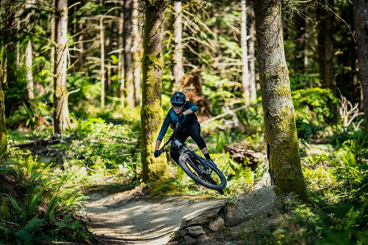 woman mountain biker jumps rock feature table at speed on new carbon liv trail bike