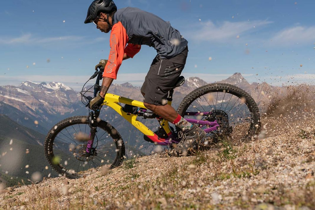 mountain bike rider drifts salsa cassidy enduro bike loose hard pack surface with mountainscape in background