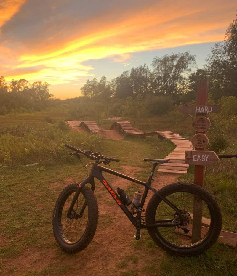 bikerumor pic of the day salsa bicycle near the trail in settlers park michigan at sunset with bright orange clouds in the sky.