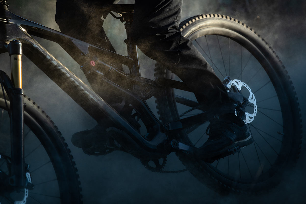 close up shot specialized stumpjumper evo being ridden through a dusty corner at speed low lighting