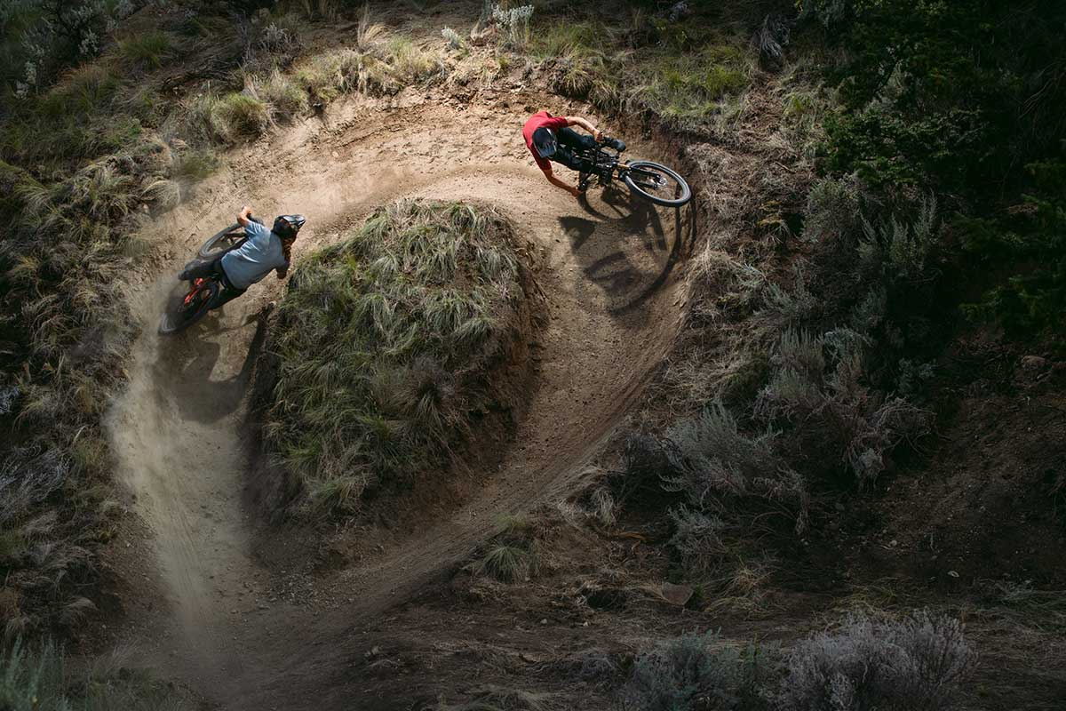 two riders carve lines through almost 360 degree berm new 150mm carbon trail bike