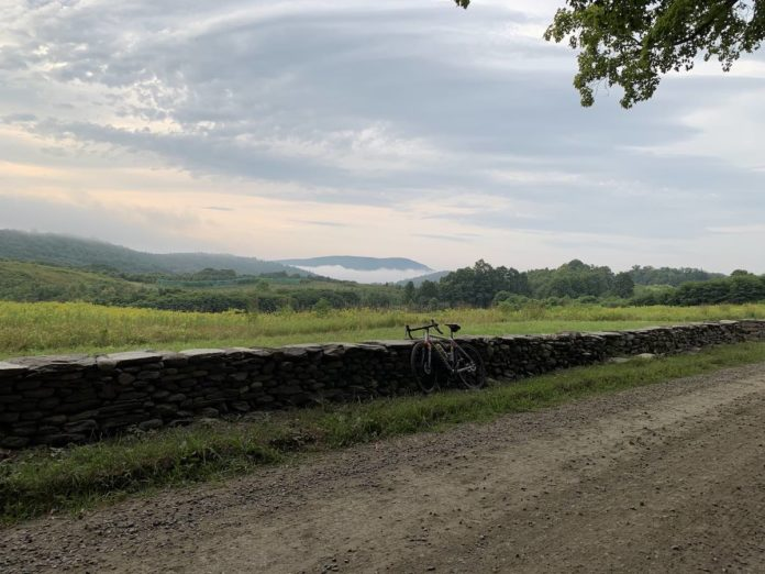 bikerumor pic of the day dummerston vermont bicycle leaning against a low stone wall next to a gravel road and with a green field on the other side of the wall with low tree line and mountains with fog on them in the distance.