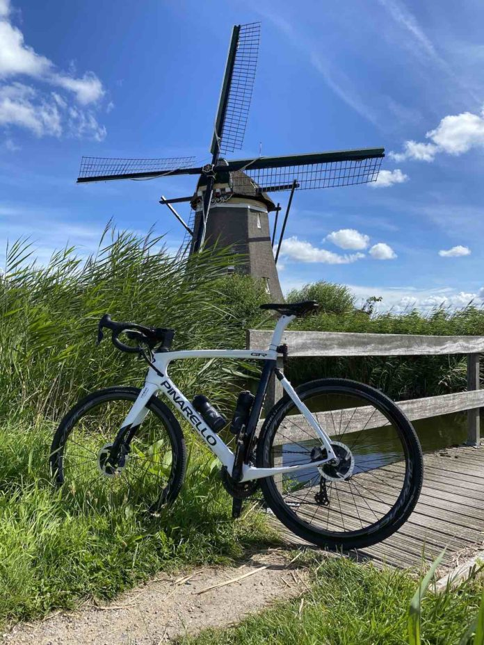 bikerumor pic of the day road bicycle leaning against a wooden bridge with high green grass on either side and a windmill in the distance with bright clear blue sky.