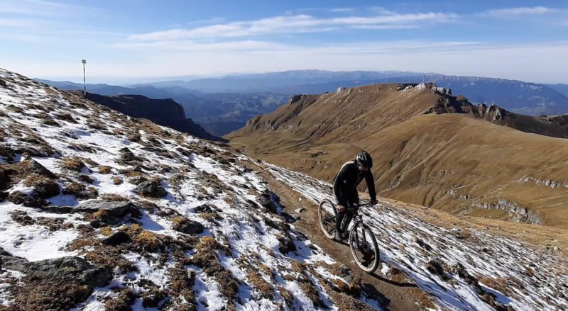 bikerumor pic of the day omg peak bucegi mountains rider is on a narrow trail with patches of snow.