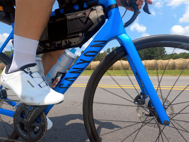 canyon endurace endurance road bike review showing bike riding with frame bags attached