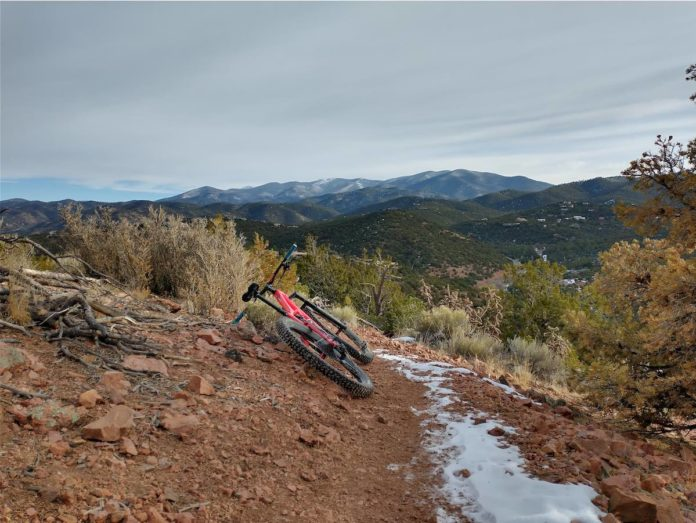 bikerumor pic of the day dale ball trails santa fe new mexico a bicycle lays on the side of a dirt and rocky trail with a bit of snow sage brush is on the side with dark green rolling mountains in the distance.