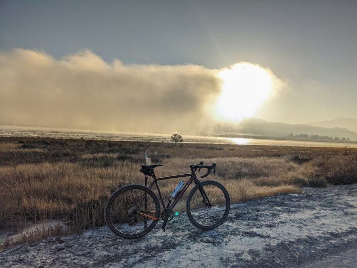 bikerumor pic of the day a vaast a/1 bicycle is posed on a dirt road with mystic lake in the distance. the sun is low and it looks like fog is just burning off the lake.