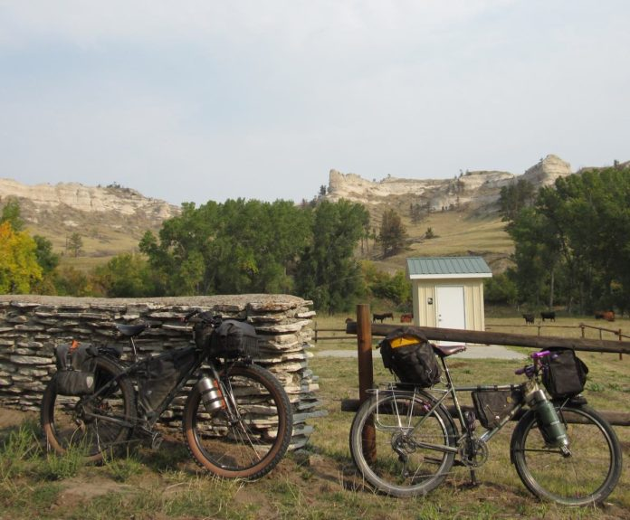 bikerumor pic of the day bikepacking in harrison nebraska. trek 820 mountain track and rawland leaning against a stone and wood fence with cows in the distance and a mountain feature sticking out above the green trees.