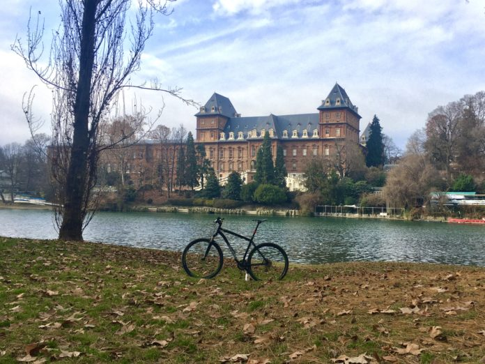 bikerumor pic of the day a bicycle on the land next to the river with a large building on the other side.