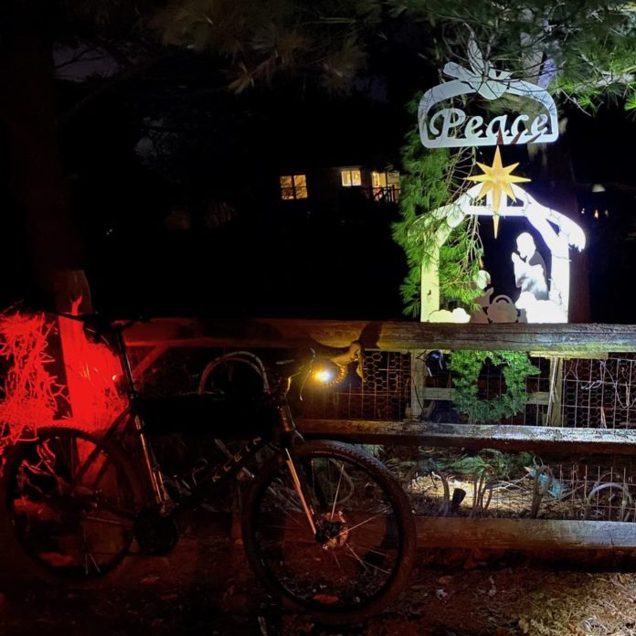 bikerumor pic of the day at night a klein bicycle is resting against a wood fence where a small metal nativity scene is placed with the word Peace above it.
