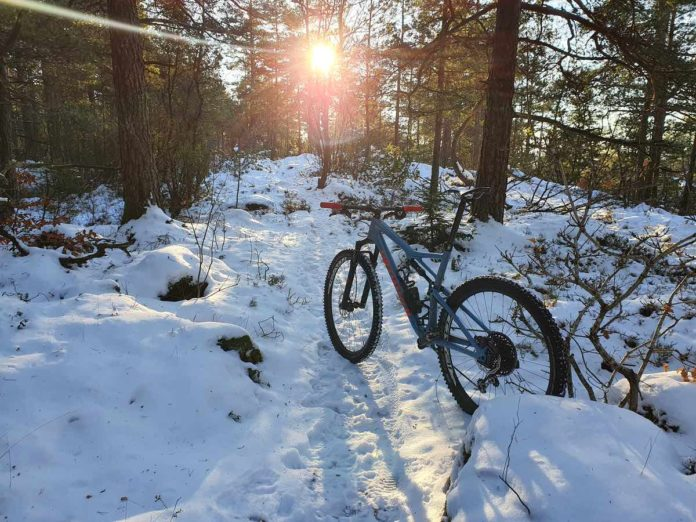 bikerumor pic of the day Tønsberg, Norway, a bicycle sits on a snowy trail with the sun peeking from behind the bare trees.