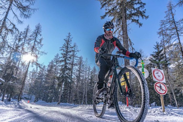 bikerumor pic of the day a mountain biker rides on compacted snow trail among pine trees on a clear sunny day in the chamonix valley france.