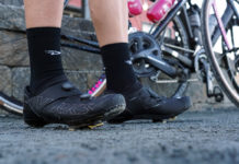 rider standing by bikes wearing specialized s-works ares road cycling shoes