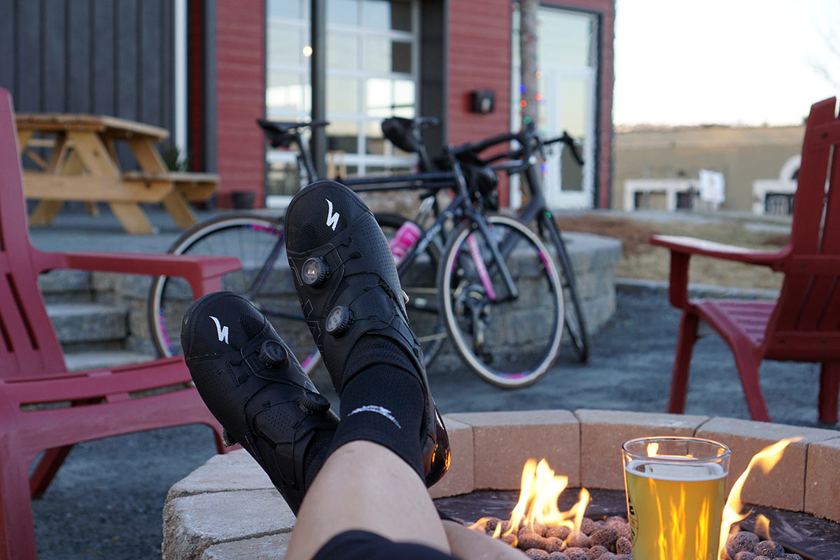 feet up on a fire pit wearing the specialized ares road cycling shoes