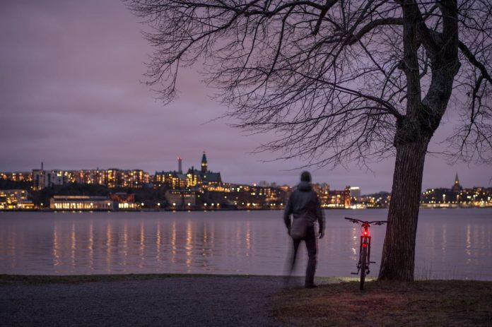 bikerumor pic of the day stockholm sweden a cyclist stands with their bike next to a tree along a river at night with the lights of Södermalm and old town on the other side of the river making the sky light up purple with the clouds