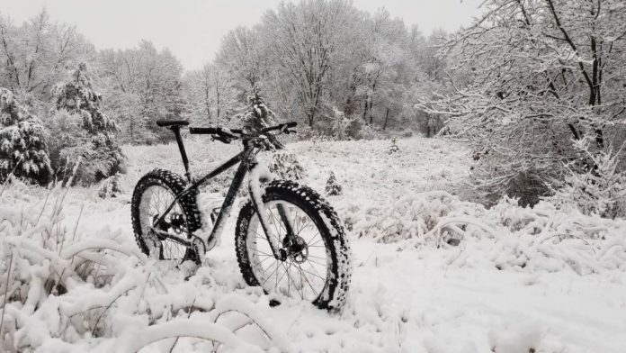 a fat bike is covered in snow, in a meadow and with trees nearby that are also covered in snow. The bike is black, so the photo looks like it is black and white.