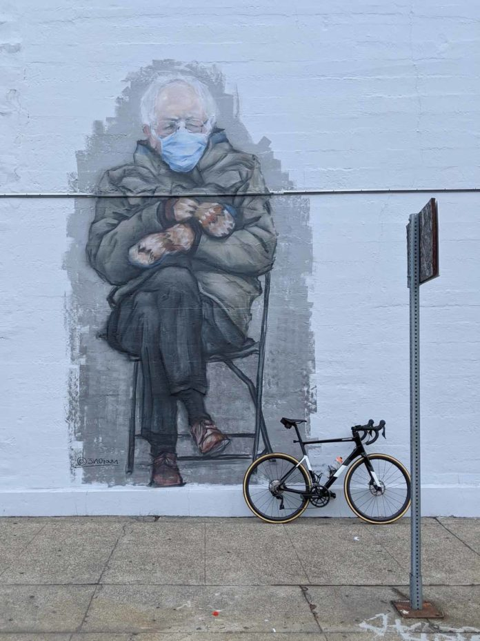bikerumor pic of the day a photo of a bicycle leaning against a wall with a giant mural of Bernie Sanders and his mittens.