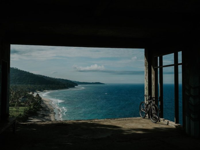 bikerumor pic of the day in West Lombok, Indonesia, a bike leans against unfinished construction overlooking the ocean and a palm tree covered coastline.