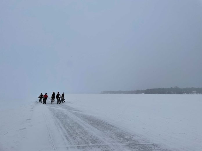bikerumor pic of the day bone saw cycling collective group of cyclists out on a frozen lake minnetonka, mn, with snow surrounding and a small batch of trees in the distance. The sky is covered in dense grey clouds.