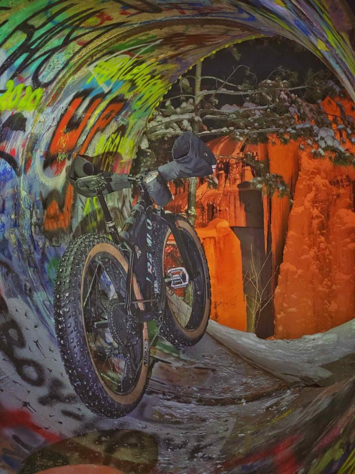 bikerumor pic of the day a fat bike is inside a drainage pipe with colorful graffiti inside and what looks like ice beyond the tunnel with an orange light on it.