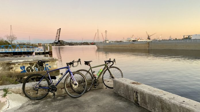 bikerumor pic of the day two bicycles lean against a concrete barrier along the elizabeth river in norfolk virginia as the sun has set and the pink sky is reflecting off the river.